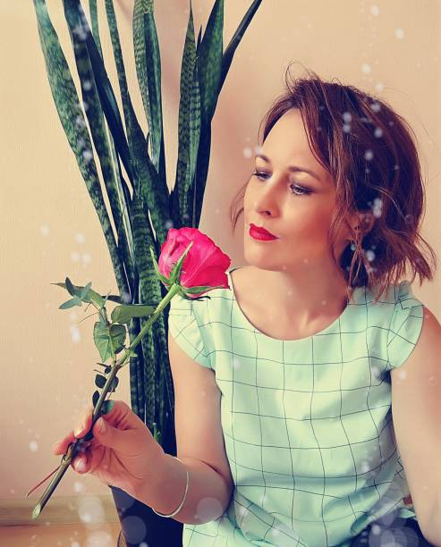 Portrait Of Beautiful Woman Holding Red Flowering Plant