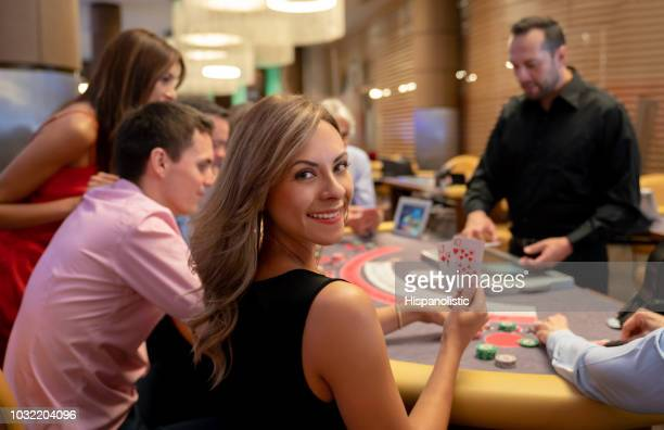 portrait of beautiful woman holding the winning cards at the blackjack table while looking at camera smiling - casino stock pictures, royalty-free photos & images