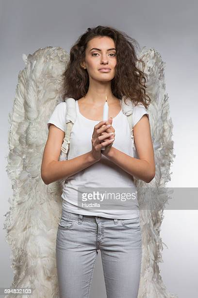 Portrait of beautiful woman in angel wings holding candle against gray background