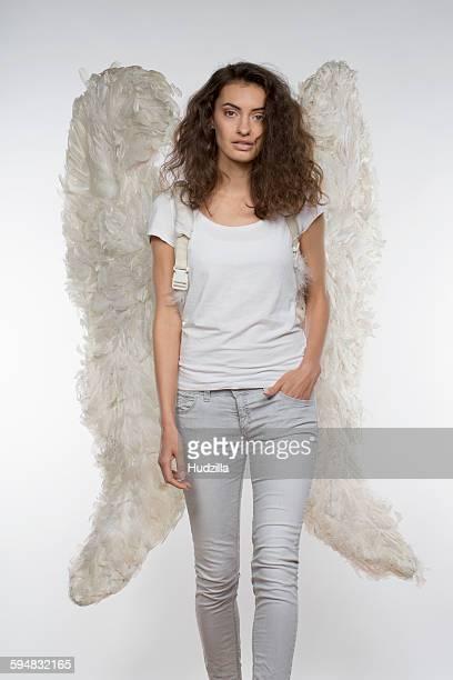 Portrait of beautiful woman in angel wings walking against white background