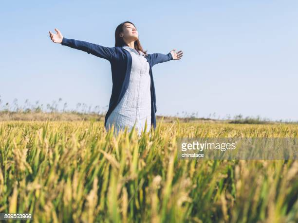Portrait of beautiful woman in field with her arms outstretched
