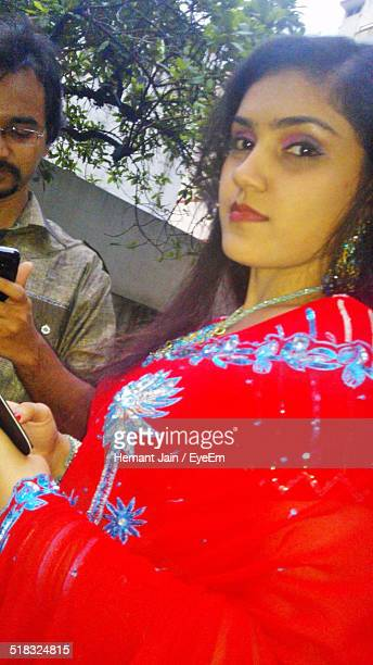 Portrait Of Beautiful Woman In Red Sari With Man Text Messaging In Background
