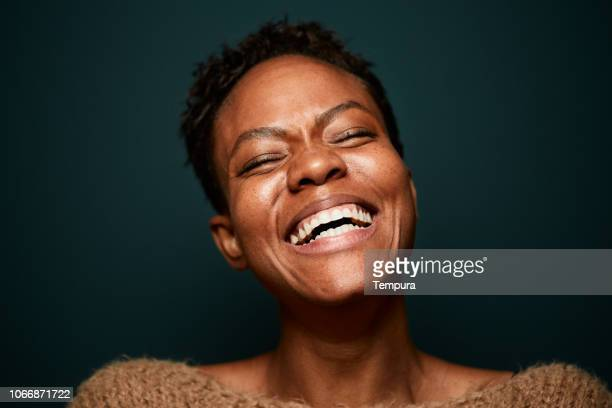 portrait of beautiful woman laughing on plain background. - adulto de idade mediana imagens e fotografias de stock