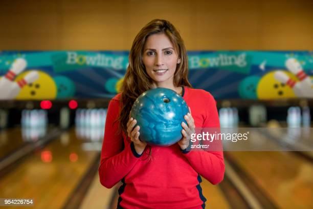 探している美しい女性の肖像画は、ボウリングのボールを押しながらカメラに焦点を当ててください。 - ボーリング場 ストックフォトと画像
