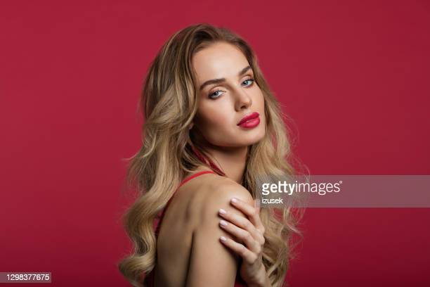 portrait of beautiful woman on red background - human back stock pictures, royalty-free photos & images