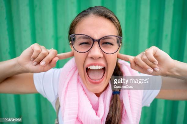 portrait of beautiful woman screaming with fingers in ears against green background - stock photo - fingers in ears stock pictures, royalty-free photos & images