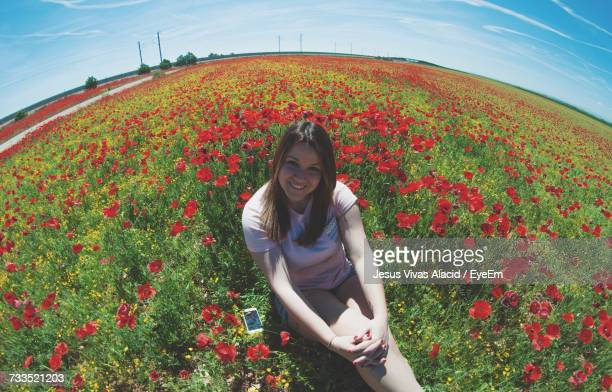 Portrait Of Beautiful Woman Sitting Amidst Red Poppies On Field