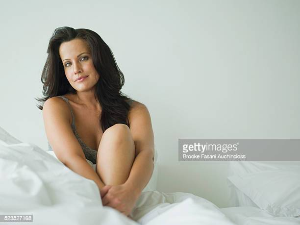 Portrait of beautiful woman sitting on bed