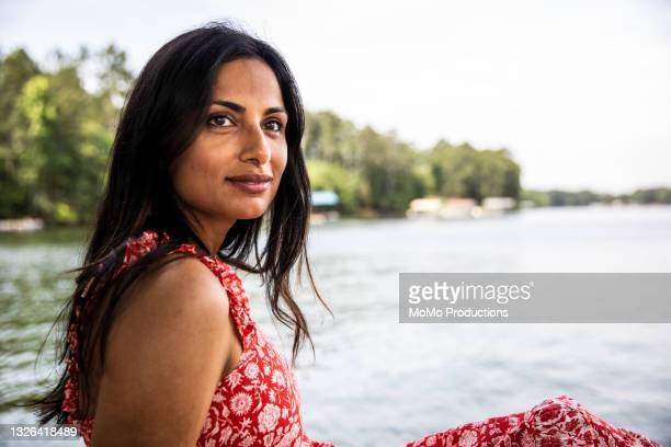 portrait of beautiful woman sitting on dock at lake - sleeveless dress stock pictures, royalty-free photos & images