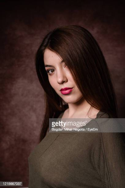 portrait of beautiful woman standing against black background - bogdan negoita stock pictures, royalty-free photos & images