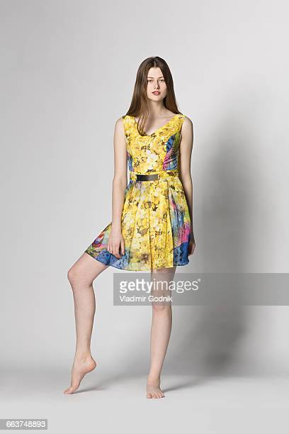 portrait of beautiful woman standing against white background - floral pattern dress stock pictures, royalty-free photos & images