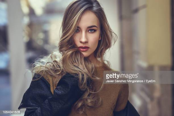 portrait of beautiful woman standing in city - leather jacket stock pictures, royalty-free photos & images