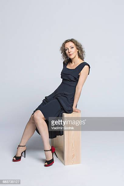 Portrait of beautiful woman wearing black dress sitting on bench against white background