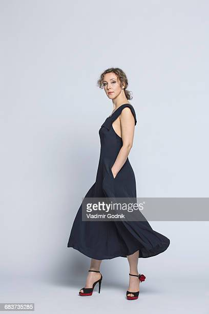portrait of beautiful woman wearing black dress standing against white background - 横からの視点 ストックフォトと画像
