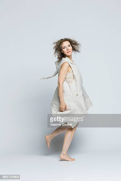 portrait of beautiful woman wearing dress spinning against white background - só adultos imagens e fotografias de stock