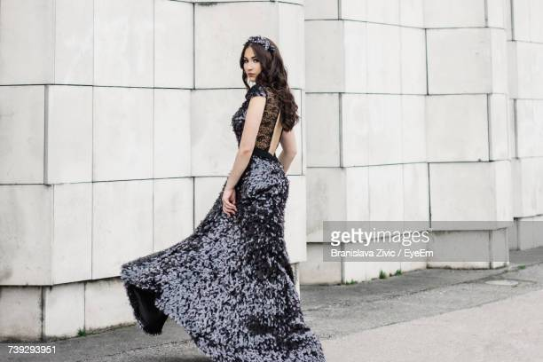 portrait of beautiful woman wearing evening gown while posing against wall - イブニングドレス ストックフォトと画像