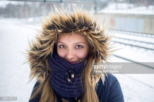 Portrait Of Beautiful Woman Wearing Fur Hood While Standing On Snow Covered Field