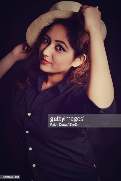 Portrait Of Beautiful Woman Wearing Hat Against Black Background