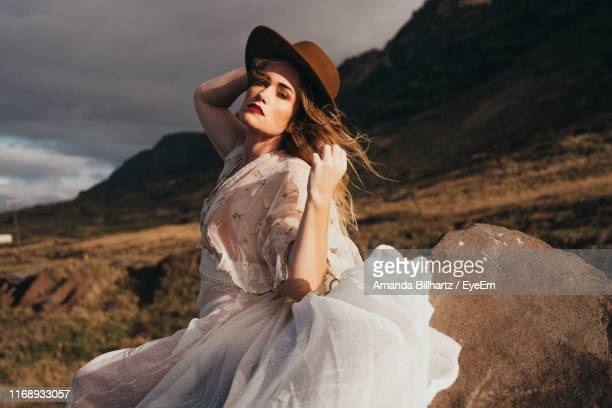 portrait of beautiful woman wearing hat while standing against sky - alta costura - fotografias e filmes do acervo