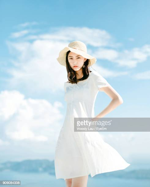 portrait of beautiful woman wearing hat while standing against sky - dress stock pictures, royalty-free photos & images