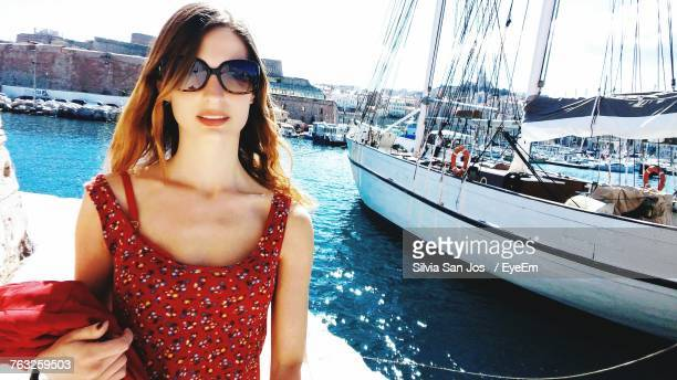 Portrait Of Beautiful Woman Wearing Sunglasses While Standing Against Ship At Harbor