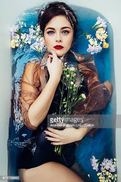 Portrait Of Beautiful Woman With Flowers In Bathtub