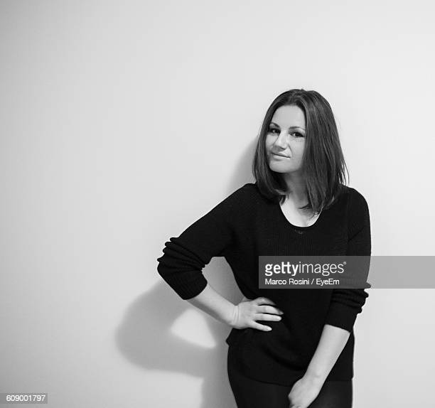 Portrait Of Beautiful Woman With Hand On Hip Leaning On Wall