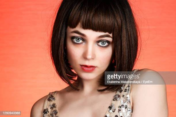 portrait of beautiful woman with short hair against orange background - gray eyes stock pictures, royalty-free photos & images