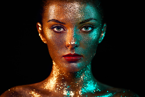 Portrait of beautiful woman with sparkles on her face 866671738