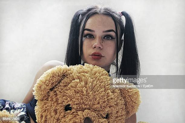 Portrait Of Beautiful Woman With Teddy Bear Against Wall