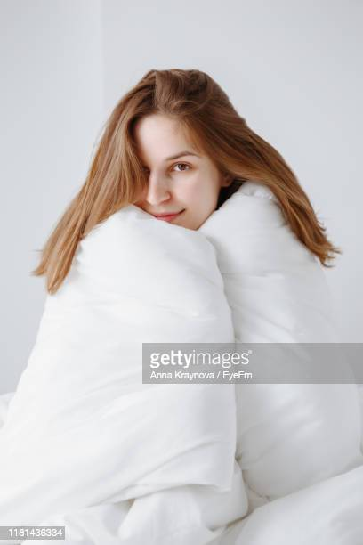 portrait of beautiful woman wrapped in duvet relaxing on bed at home - avvolto in una coperta foto e immagini stock