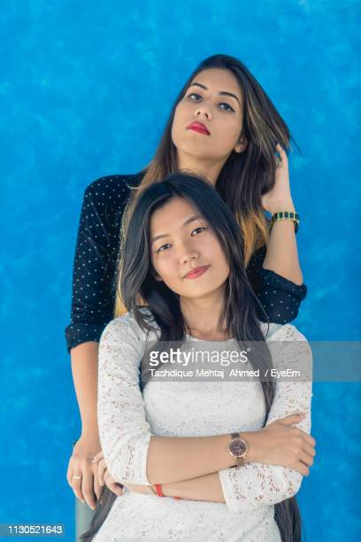 portrait of beautiful women standing against blue wall - guwahati stock pictures, royalty-free photos & images