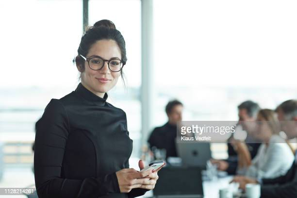 portrait of beautiful young businesswoman in meeting room - image focus technique stock pictures, royalty-free photos & images