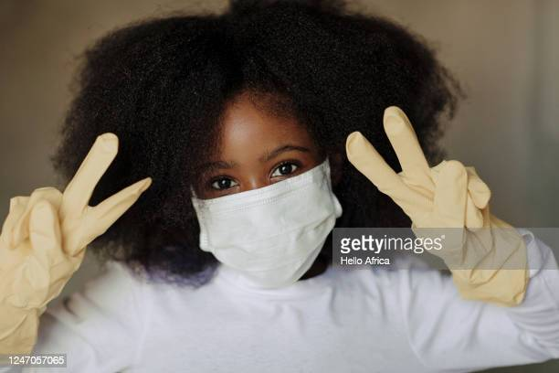 portrait of beautiful young girls wearing face mask looking at camera showing victory signs - south africa stock pictures, royalty-free photos & images
