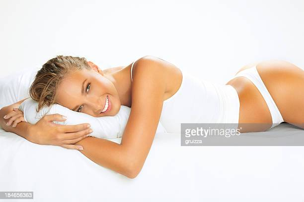 Portrait of beautiful, young, smiling woman on bed, hugging pillow