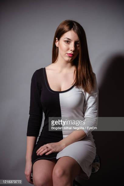 portrait of beautiful young woman against black background - bogdan negoita stock pictures, royalty-free photos & images