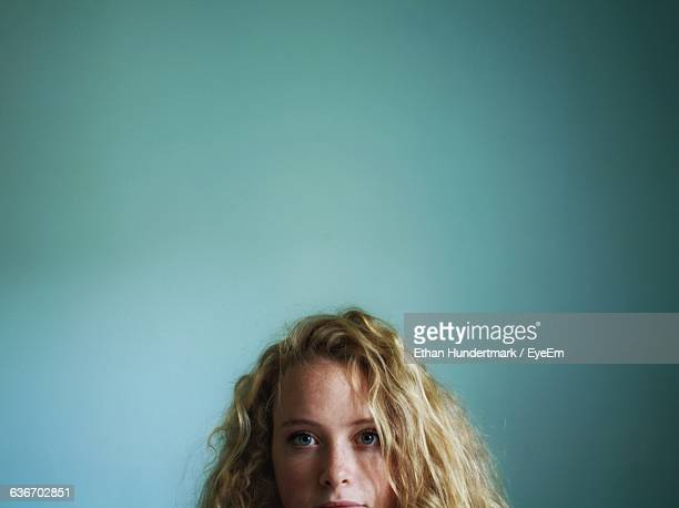 Portrait Of Beautiful Young Woman Against Blue Wall