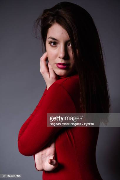 portrait of beautiful young woman against gray background - bogdan negoita stock pictures, royalty-free photos & images