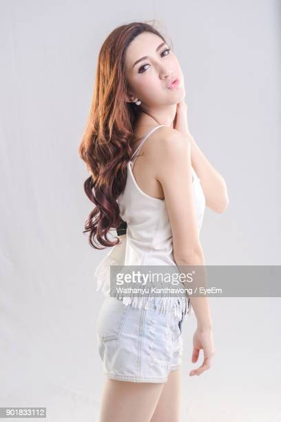 portrait of beautiful young woman against gray background - sleeveless stock pictures, royalty-free photos & images