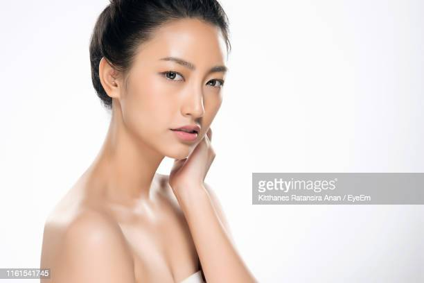 portrait of beautiful young woman against white background - off shoulder stock pictures, royalty-free photos & images