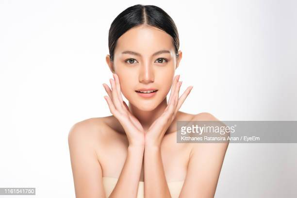 portrait of beautiful young woman against white background - 人の肌 ストックフォトと画像