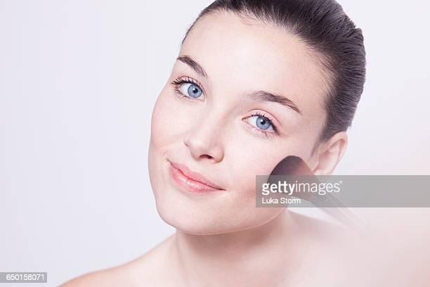 Portrait of beautiful young woman applying blusher