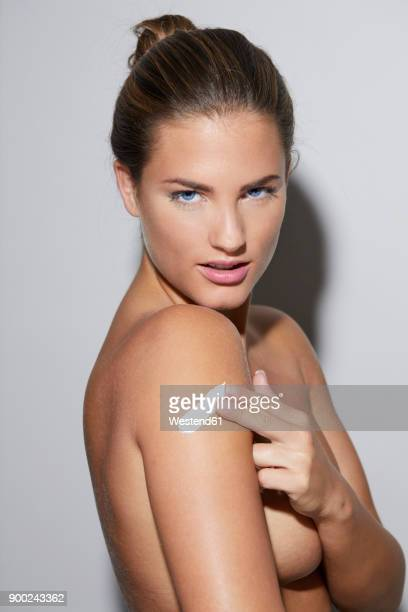 Portrait of beautiful young woman applying skin cream on her arm