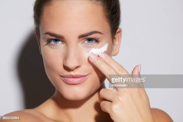 Portrait of beautiful young woman applying skin cream