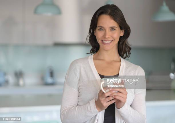 Portrait of beautiful young woman at home holding a warm cup of tea smiling at camera