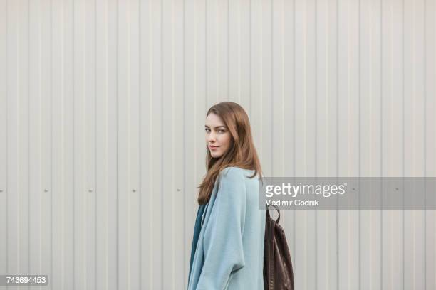 Portrait of beautiful young woman carrying backpack while standing by wall