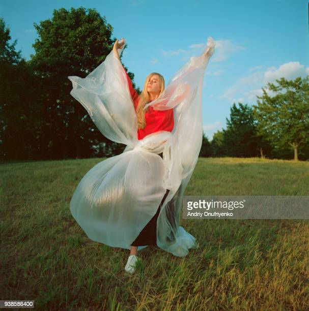 Portrait of beautiful young woman dancing in a meadow