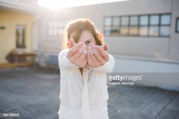 Portrait of beautiful young woman dancing with hands reaching out on sunlit roof terrace