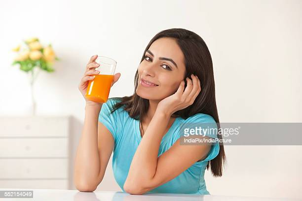 portrait of beautiful young woman drinking orange juice at home - at home ストックフォトと画像