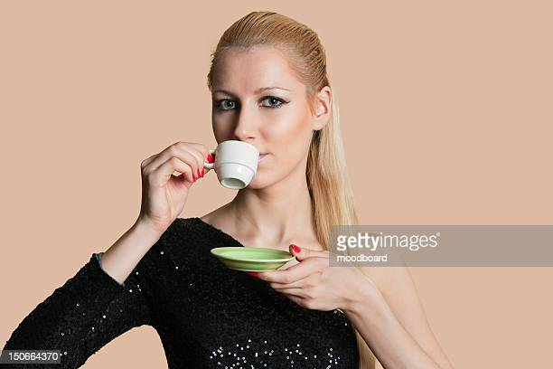 portrait of beautiful young woman drinking tea over colored background - platillo fotografías e imágenes de stock
